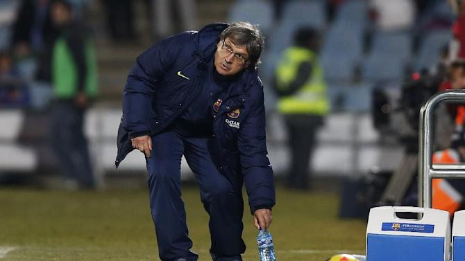 FC Barcelona's coach Gerardo 'Tata' Martino from Argentina picks up a bottle of water during a Spanish La Liga soccer match between FC Barcelona and Getafe at the Coliseum Alfonso Perez stadium in Madrid, Spain, Sunday, Dec. 22, 2013