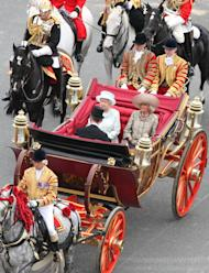 Britain's Queen Elizabeth facing camera left, with Prince Charles and Camilla Duchess of Cornwall, ride in a carriage as they head for Buckingham Palace in a carriage procession in London Tuesday June 5, 2012. The carriage procession is part of a four-day Diamond Jubilee celebration to mark the 60th anniversary of Queen Elizabeth II accession to the throne (AP Photo/Elizabeth Dalziel/Pool)