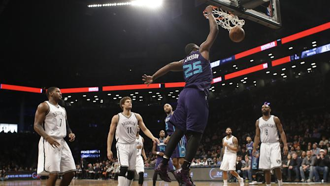 Brooklyn Nets' Joe Johnson (7), Brook Lopez (11) and Alan Anderson (6) watch as Charlotte Hornets' Al Jefferson (25) dunks the ball during the first half of an NBA basketball game Wednesday, March 4, 2015, in New York. (AP Photo/Frank Franklin II)
