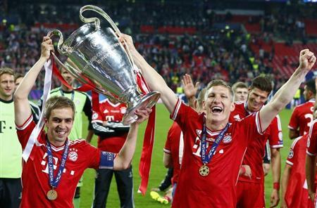 Bayern Munich's Lahm and Schweinsteiger celebrate with the Champions League Trophy after defeating Borussia Dortmund in their Champions League Final match at Wembley Stadium in London