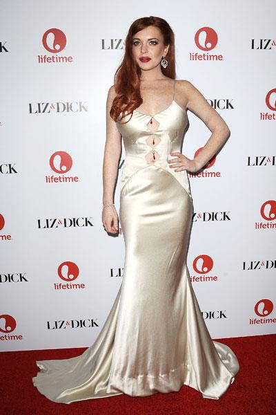 """Elizabeth Taylor she is not. Lindsay Lohan steps out in a dress that's just barely hanging on to her at the """"Liz & Dick"""" premiere on Nov. 20 in Beverly Hills. The gold-champagne coloured gown squeezes Lohan's frame, making the cut-outs bulge. And what's with the three Christmas decorations on her torso? Is she celebrating the holidays early? This isn't Hollywood glam, it's a Hollywood tragedy. (Photo by Jason LaVeris/FilmMagic)"""