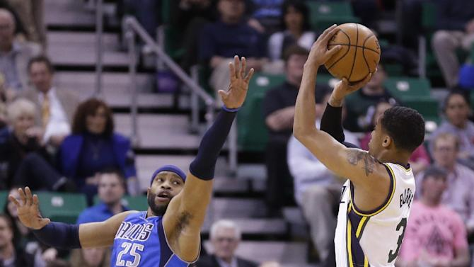 Utah Jazz's Trey Burke (3) shoots as Dallas Mavericks' Vince Carter (25) defends in the first quarter during an NBA basketball game Wednesday, March 12, 2014, in Salt Lake City