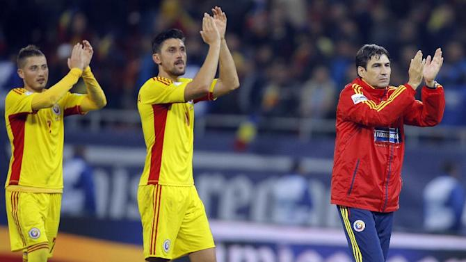 Romania's Ciprian Marica, center, applauds supporters with coach Victor Piturca, right, and teammate Gheorghe Grozav at the end of the World Cup Group D qualifying soccer match against Estonia at the National Arena stadium in Bucharest, Romania, Tuesday, Oct. 15, 2013