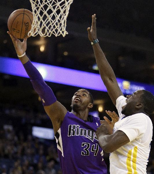 Sacramento Kings' Jason Thompson (34) lays up a shot past Golden State Warriors' Draymond Green during the first half of an NBA basketball game on Saturday, Nov. 2, 2013, in Oakland, Calif