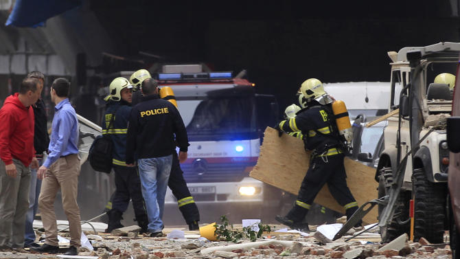 Policemen and firefighters inspect the scene of an explosion in downtown Prague, Czech Republic, Monday, April 29, 2013.  Police said a powerful explosion has damaged a building in the center of the Czech capital and they believe some people are buried in the rubble. (AP Photo/Petr David Josek)