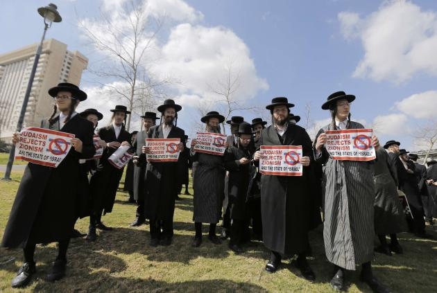 Members of Neturei Karta hold signs during a protest in Jerusalem