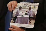 Israeli Prime Minister Benjamin Netanyahu shows a picture that was given to him as a gift by US Secretary of State John Kerry during a meeting in Jerusalem, on May 23, 2013. Kerry flew in to Jerusalem as he kept up a push to bring Israelis and Palestinians back to peace negotiations amid a growing scepticism over his efforts. AFP PHOTO/POOL/JIM YOUNG