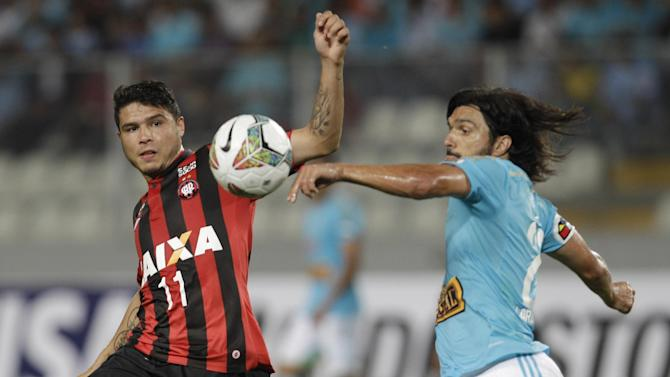 Zezinho of Brazil's Atletico Paranaense, left, fights for the ball with Jorge Cazulo of Peru's Sporting Cristal during a Copa Libertadores soccer match in Lima, Peru, Wednesday, Jan. 29, 2014