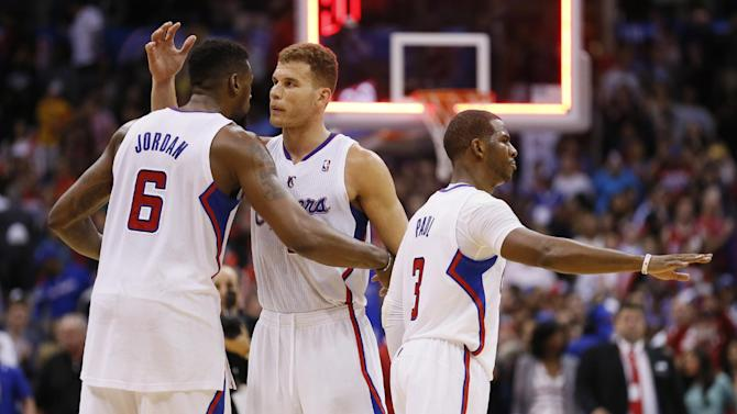 Los Angeles Clippers' DeAndre Jordan, left, Blake Griffin, center, and Chris Paul, right, celebrate the team's victory against the Golden State Warriors at the end of an NBA basketball game in Los Angeles, Wednesday, March 12, 2014. The Clippers won 111-98