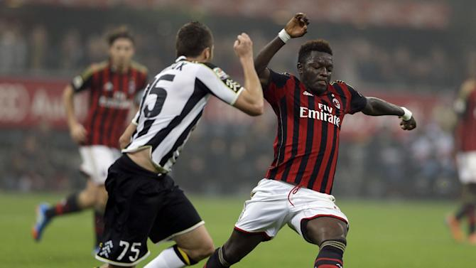 AC Milan's Sulley Muntari, right, is tackled by Udinese defender Thomas Heurtaux during a Serie A soccer match between AC Milan and Udinese, at the San Siro stadium in Milan, Italy, Saturday, Oct. 19, 2013