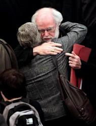 """Archbishop of Canterbury Rowan Williams hugs a female member of the clergy at Church House in central London on November 20. The Church of England has """"undoubtedly"""" lost credibility after voting to reject the appointment of women bishops, its leader the Archbishop of Canterbury said Wednesday."""