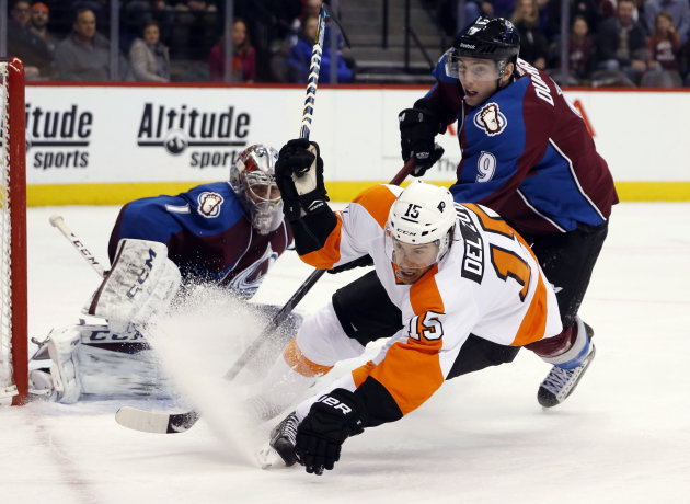 Philadelphia Flyers defenseman Michael Del Zotto, front, falls to the ice after being checked during a rush to the net for a shot by Colorado Avalanche center Matt Duchene, right, as goalie Semyon Varlamov, of Russia, looks on in the second period of an NHL hockey game Wednesday, Dec. 31, 2014, in Denver. (AP Photo/David Zalubowski)