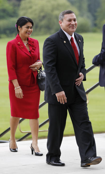 FILE - In this July 27, 2012 file photo, Guam Gov. Eddie Baza Calvo and his wife Christine Lujan Sonido arrive at Buckingham Palace in London for a reception hosted by Queen Elizabeth II prior to the