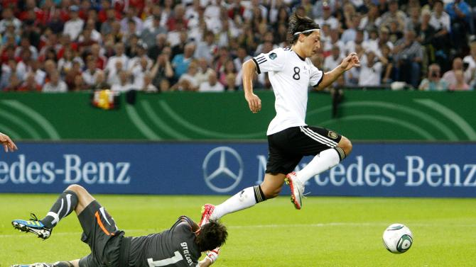 Germany's Mesut Oezil, right, passes Austrian goal keeper Christian Gratzei to score his side's 2nd goal during the Euro 2012 Group A qualifying soccer match between Germany and Austria in Gelsenkirchen, Germany, Friday, Sept. 2, 2011.  (AP Photo/Michael Probst)