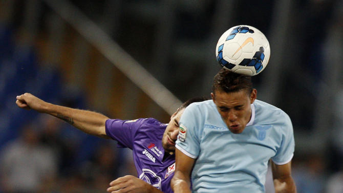 Fiorentina defender Nenad Tomovic, of Serbia, left, and Lazio forward Brayan Perea, of Colombia, jump for a header during a Serie A soccer match between Lazio and Fiorentina, at Rome's Olympic stadium, Sunday, Oct. 6, 2013