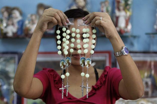 A shop worker poses as she holds up rosaries bearing pictures of Pope John Paul II inside a religious store in Caloocan city, metro Manila