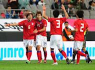 Park Jong-Woo (L) celebrates with teammates after scoring against Uzbekistan's national U-23 team during a match in Seoul in 2011. He will be excused military service despite controversially displaying a sign on a territorial dispute at the Olympic Games, the head of conscription said on Friday