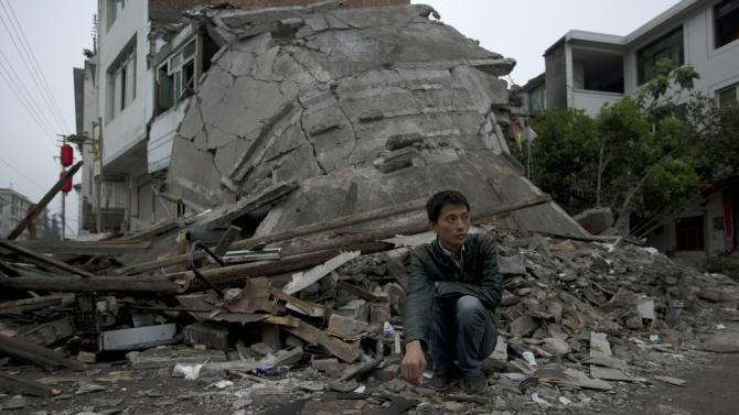 A man squats near the collapsed remains of a building destroyed by Saturday's earthquake in Lushan county in southwestern China's Sichuan province, Monday, April 22, 2013. Saturday's earthquake in Sichuan province killed at least 186 people, injured more than 11,000 and left nearly two dozen missing, mostly in the rural communities around Ya'an city, along the same seismic fault where a devastating quake to the north killed more than 90,000 people in Sichuan and neighboring areas five years ago in one of China's worst natural disasters.(AP Photo/Ng Han Guan)