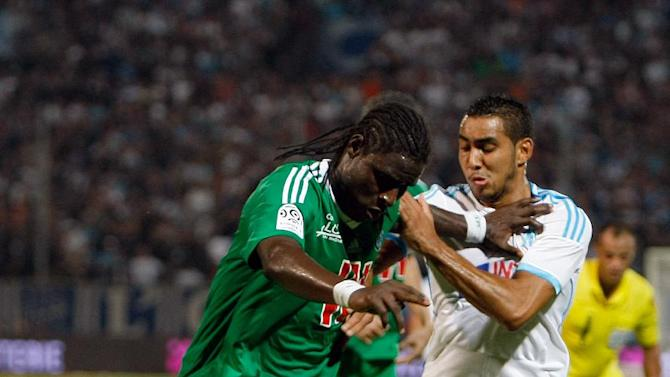 Saint-Etienne's Senegalese defender Moustapha Sall, left, challenges for the ball with Marseille's French forward Dimitri Payet during their League One soccer match at the Velodrome Stadium, in Marseille, southern France, Tuesday, Sept. 24, 2013