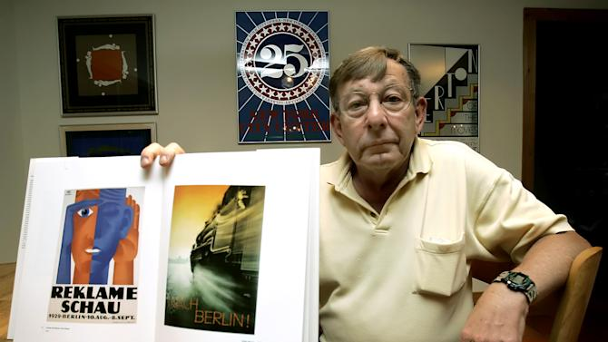 FILE - In this May 16, 2006 file photo Peter Sachs holds up a book with some of his father, Hans Sachs' favorite posters at his home in Sarasota, Fla.  Seized by the Nazis in 1938 from a Jewish man on the orders of Hitler's Propaganda Minister Joseph Goebbels, then held behind the Iron Curtain in Communist East Berlin, thousands of rare posters are finally back in the hands of collector Hans Sachs' family. After a seven-year battle for their return from a German museum where they ended up after the fall of the Berlin Wall, almost entirely tucked away in storage, Sachs' heir,  told The Associated Press he hopes auctioning off the majority of the posters will mean they will finally be on display for those who love them like his father did, after he failed to find a museum willing to take the whole collection on. (AP Photo/Chris O'Meara,File)
