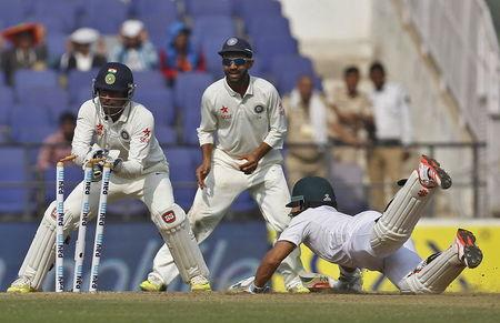 India's wicketkeeper Saha makes an unsuccessful attempt to run-out South Africa's Duminy as India's Rahane watches during the third day of their third test cricket match in Nagpur