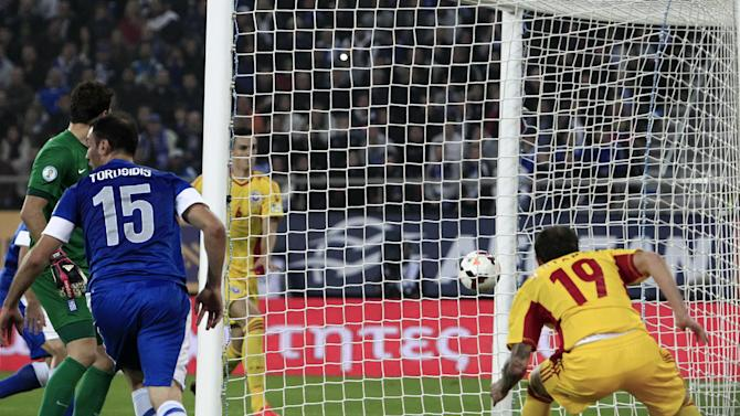 Romania's Bogdan Sorin Stancu, right, scores against Greece during their World Cup qualifying playoff first leg soccer match at the Karaiskaki stadium in the port of Piraeus, near Athens, Friday, Nov. 15, 2013