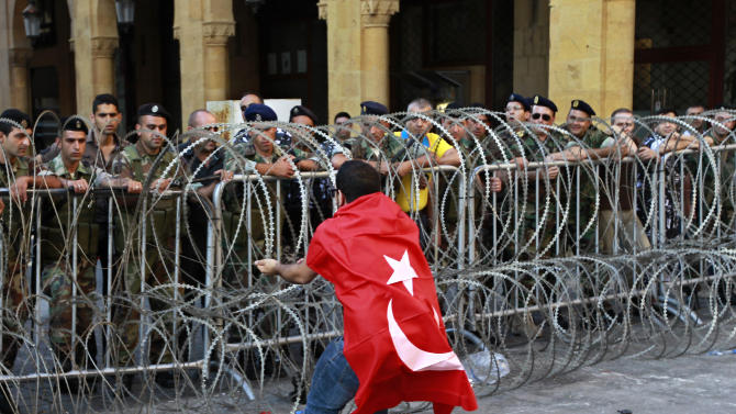 A civil society protester tries to remove barbed wire while wearing a Turkish flag during a demonstration protesting the extension of parliament's mandate, near Parliament in Beirut, Lebanon, Friday, June 21, 2013. Lebanon's parliament on May 29 extended its term by a year and a half, skipping scheduled elections because of the country's deteriorating security linked to the civil war next door in Syria. (AP Photo/Bilal Hussein)