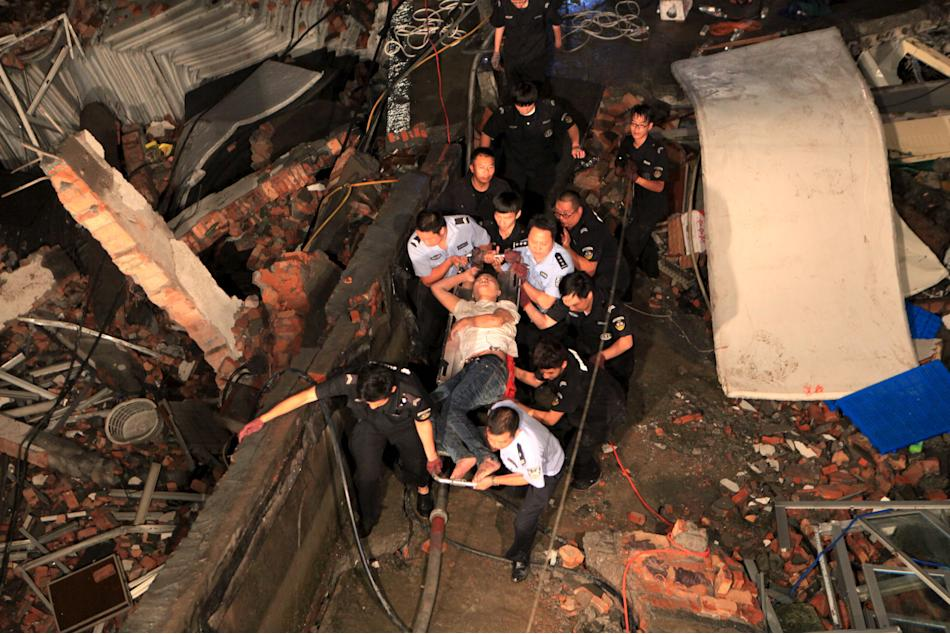 Rescue workers carry out an injured man after a shoe factory building collapsed in Wenling