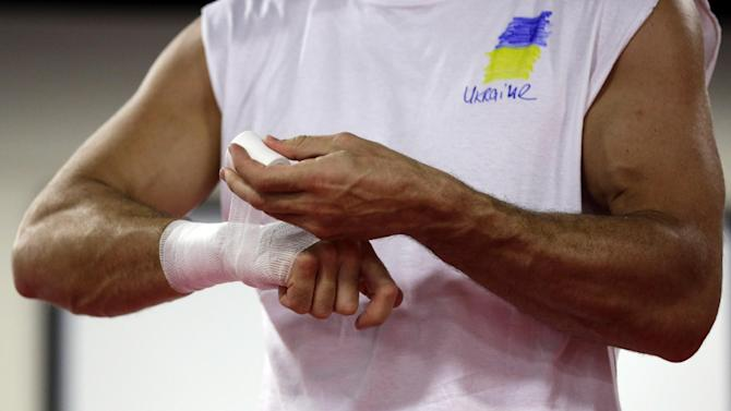 Heavyweight boxing champion Wladimir Klitschko, of Ukraine, tapes his hands while training at the Lucky Street Boxing Gym, Thursday, March 20, 2014, in Hollywood, Fla. Klitschko is preparing for his April 26 title fight against Alex Leapai in Germany