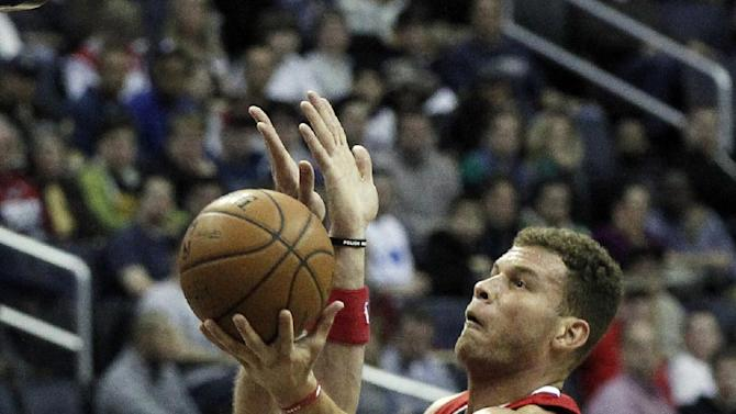 Los Angeles Clippers forward Blake Griffin (32) shoots over Washington Wizards center Marcin Gortat (4), from Poland, in the first half of an NBA basketball game, Saturday, Dec. 14, 2013, in Washington