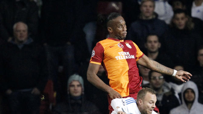 Galatasaray's Didier Drogba, back, and FC Copenhagen's Lars Jacobsen compete for the ball during their Champions League Group B soccer match at Parken Stadium, Copenhagen, Denmark, Tuesday, Nov. 5, 2013