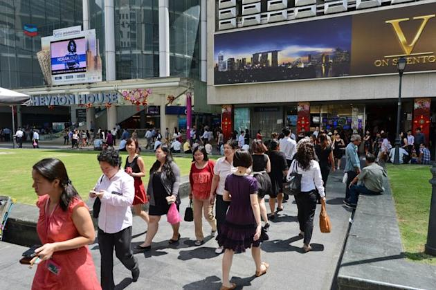 Pedestrians walk down a street in downtown financial district in Singapore on January 29, 2013. Singapore's population may reach almost seven million by 2030, up from 5.31 million currently, with the number of citizens shrinking to barely half of the total, the government said