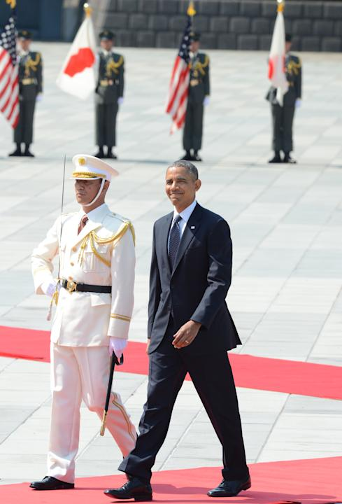 U.S. President Barack Obama smiles as he inspects the honor guard during a welcoming ceremony at the Imperial Palace in Tokyo Thursday, April 24, 2014. Facing fresh questions about his commitment to A