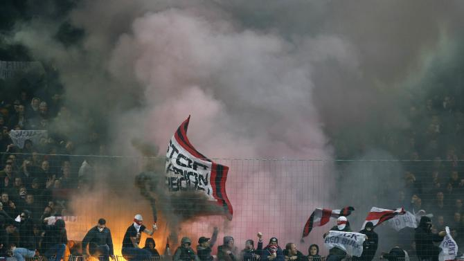 Ajax Amsterdam supporters light flares during the team's Europa League soccer match against FC Salzburg in Salzburg