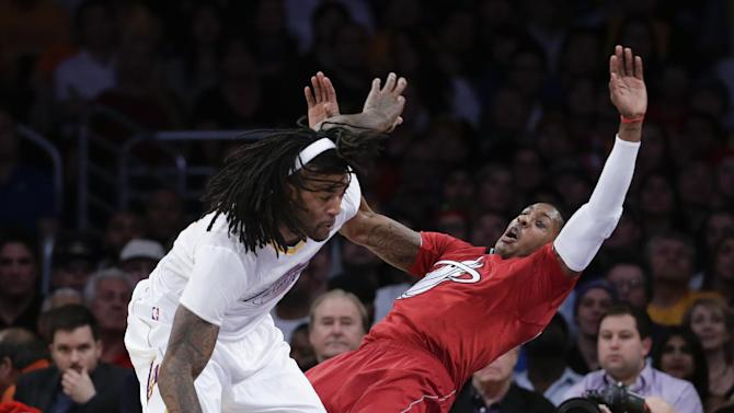 Los Angeles Lakers center Jordan Hill, left, pushes Miami Heat guard Dwyane Wade during the second half of an NBA basketball game in Los Angeles, Wednesday, Dec. 25, 2013. Hill received an offensive foul on the play