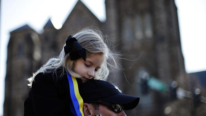 Marathon runner Nathan Finney of Boston and his daughter Mckenna, 5, gather with others ahead of an interfaith service with President Barack Obama at Cathedral of the Holy Cross, held in the wake of Monday's Boston Marathon explosions, which killed at least three and injured more than 140, Thursday, April 18, 2013, in Boston. (AP Photo/Matt Rourke)