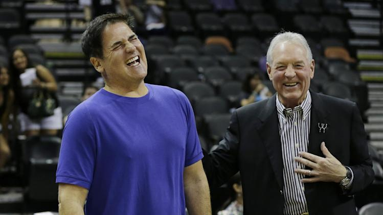 Dallas Mavericks owner Mark Cuban, left, and San Antonio Spurs owner Peter Holt, right, laugh before Game 2 of the opening-round NBA basketball playoff series on Wednesday, April 23, 2014, in San Antonio
