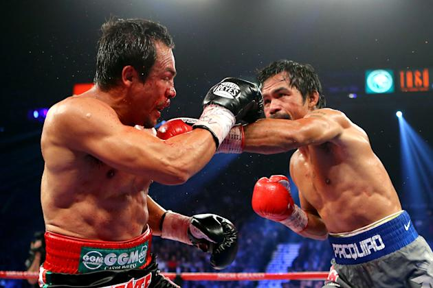 LAS VEGAS, NV - DECEMBER 08: (R-L) Manny Pacquiao throws a left at Juan Manuel Marquez during their welterweight bout at the MGM Grand Garden Arena on December 8, 2012 in Las Vegas, Nevada. (Photo by Al Bello/Getty Images)