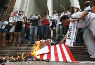 Student activist Marjohara Tucay, right, who heckled U.S. Secretary of State Hillary Rodham Clinton during her town hall meeting and interview in Manila Wednesday, adjusts a burning mock American flag, during a protest Thursday, Nov. 17, 2011 at the University of the Philippines campus in Diliman, Quezon city, northeast of Manila, Philippines. On Thursday, Philippine Defense Secretary Voltaire Gazmin said the United States will provide a second warship to the ill-equipped Philippine military as its longtime Asian ally confronts China in increasingly territorial disputes in the South China Sea. (AP Photo/Bullit Marquez)