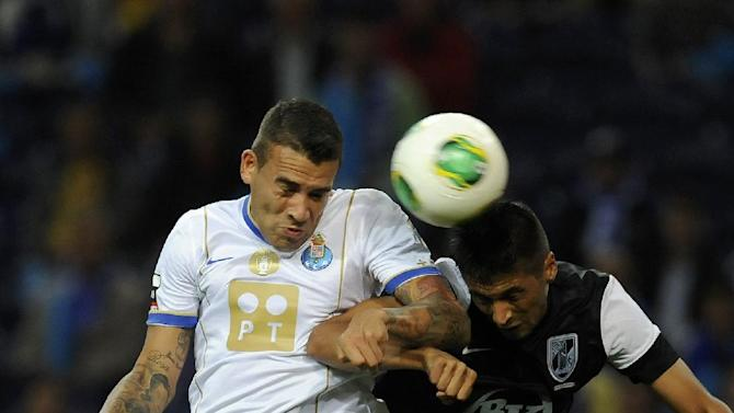 """FC Porto's Nicolas Otamendi, from Argentina, challenges for a high ball with Vitoria Guimaraes' Joao """"Moreno"""" Teixeira, right, in a Portuguese League soccer match at the Dragao Stadium in Porto, Portugal, Friday, Sept. 27, 2013"""