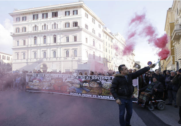 "Demonstrators hold up a banner reading in Italian ""No to austerity policies. No to Renzi's government. Never with Matteo Salvini, Rome does not want you"" during a counter-demonstration a"