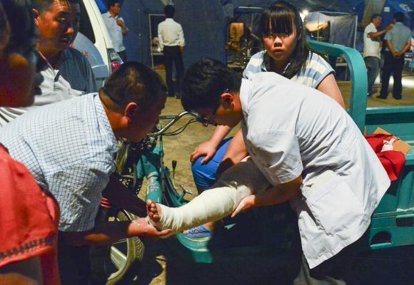 PISHAN, July 4, 2015 (Xinhua) -- Doctors treat injured residents in a tent in Pishan County of Hotan Prefecture, northwest China's Xinjiang Uygur Autonomous Region, July 4, 2015. A 6.5-magnitude e