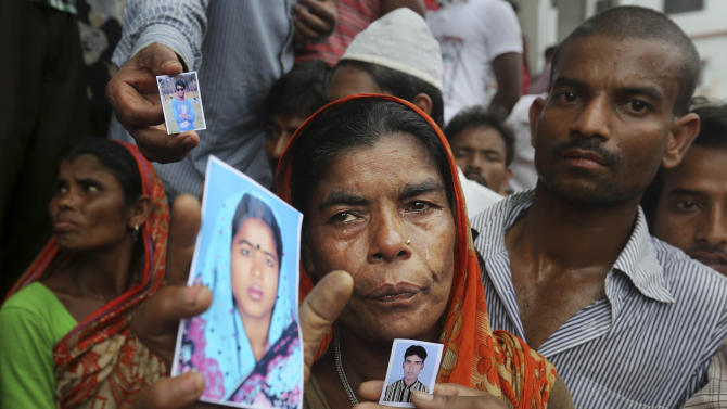 A Bangladeshi weeps as she holds a picture of a missing relative with others at the site of a building that collapsed Wednesday in Savar, near Dhaka, Bangladesh, Thursday, April 25, 2013. By Thursday, the death toll reached at least 194 people as rescuers continued to search for injured and missing, after a huge section of an eight-story building that housed several garment factories splintered into a pile of concrete. (AP Photo/Kevin Frayer)