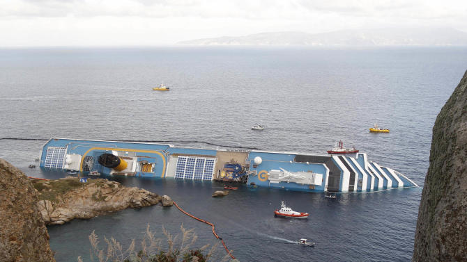 In this , Sunday, Jan. 22, 2012 file photo, the cruise ship Costa Concordia lies on its side off the Tuscan island of Giglio, Italy. Costa Crociere SpA says work to remove the capsized Costa Concordia cruise ship from its rocky perch off Tuscany will begin early next month and is expected to take 12 months. Costa said in a statement Saturday, April 21, 2012, the U.S.-owned company Titan Salvage won the bid to remove the ship, which struck rocks off the tourist-dependent island of Giglio on Jan. 13, when the captain made an unauthorized maneuver too close to shore. (AP Photo/Pier Paolo Cito, File)