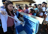 A church group distributes food to displaced victims of Typhoon Bopha at an evacuation centre in Maparat, Compostela Valley. The typhoon that has killed hundreds of people and left tens of thousands homeless in the southern Philippines has turned back towards the country and will hit it again, forecasters say