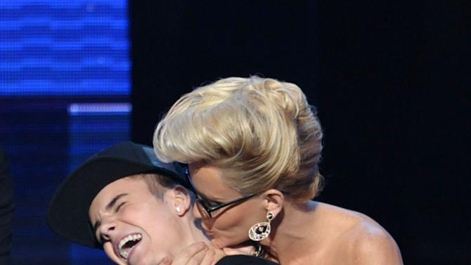 """Justin Bieber is smothered in kisses by presenter Jenny McCarthy as he accepts the award for favorite album - pop/rock for """"Believe"""" at the 40th Anniversary American Music Awards on Sunday, Nov. 18, 2012, in Los Angeles. (Photo by John Shearer/Invision/AP)"""