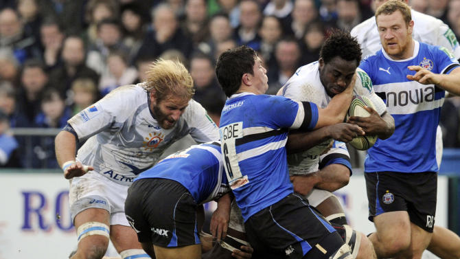 Bath's Francois Louw, centre, and Olly Woodburn, 2nd left, tackle Montpellier's Remy Martin during their Heineken Cup pool 3 rugby match at the Recreation ground, Bath, England, Sunday, Nov. 20, 2011. (AP Photo/Tom Hevezi)
