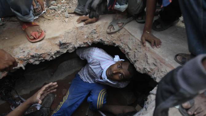 A Bangladeshi rescuer looking for survivors emerges from beneath a concrete slab of a building that collapsed Wednesday in Savar, near Dhaka, Bangladesh,Thursday, April 25, 2013. By Thursday, the death toll reached at least 194 people as rescuers continued to search for injured and missing, after a huge section of an eight-story building that housed several garment factories splintered into a pile of concrete. (AP Photo/A.M.Ahad)