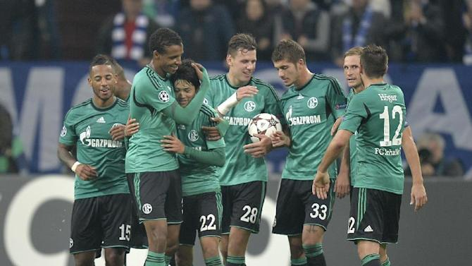 Schalke's Atsuto Uchida, no. 22, is hugged by Schalke's Joel Matip as he celebrates with teammates after scoring the opening goal during the Champions League Group E soccer match between FC Schalke 04 and Steaua Bucharest  in Gelsenkirchen, Germany, Wednesday, Sept. 18, 2013
