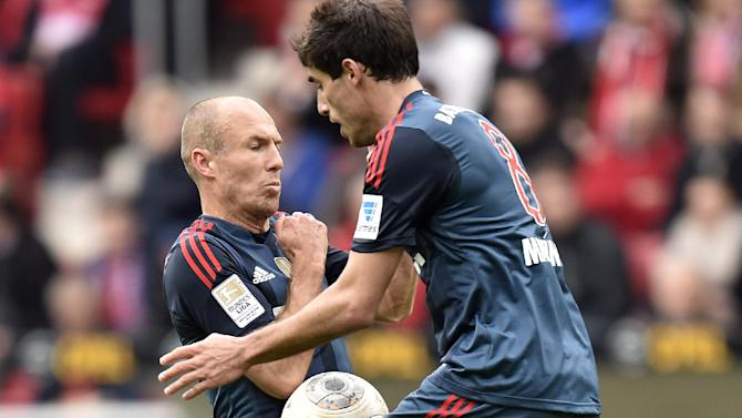 Bayern's Arjen Robben of the Netherlands, left, and Bayern's Javier Martinez of Spain jump for the ball during  the German Bundesliga soccer match between FSV Mainz 05 and Bayern Munich in Mainz,  Germany, Saturday, March 22, 2014